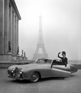 131 Tony Linck, Model posing next to Delahaye auto with Eiffel Tower in background