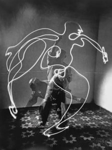 162 - Gjon Mili, Multiple exposure of the artist Pablo Picasso using flashlight to make light drawing of a figure in the air that appears to be a man running