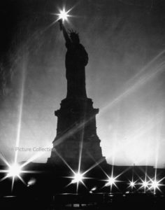 Andreas Feininger (Crystalline night surrounding the Statue of Liberty w. diamonds of star-like light from her torch and lampposts during WWII blackout.