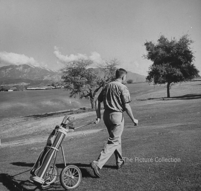 Edward Clark (A man operating his own caddy pulling the bicycle wheeled cart full of golf clubs across the golf course) US, California 1953